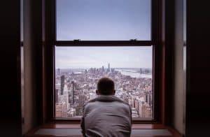 Mann schaut aus dem Fenster in die Ferne