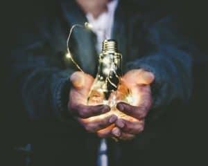 Mann streckt die Hand aus und hält eine Glühbirne in der Hand