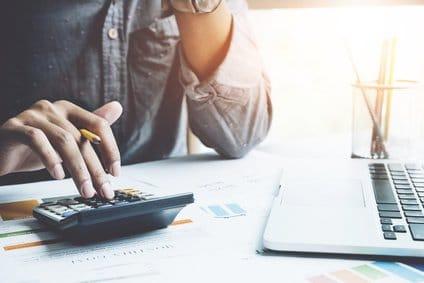 Schließen Sie einen Mann, der mit einem Taschenrechner in seinem Büro arbeitet, um das Abrechnungsjahr zu berechnen.