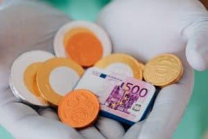 Frau hält in ihrer Hand Süßigkeiten die aussehen wie Geld