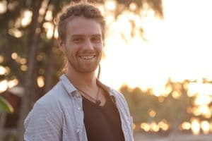 Schöner lachender Mann mit Hemd, Kette und Dreadlocks bei Sonnenuntergang