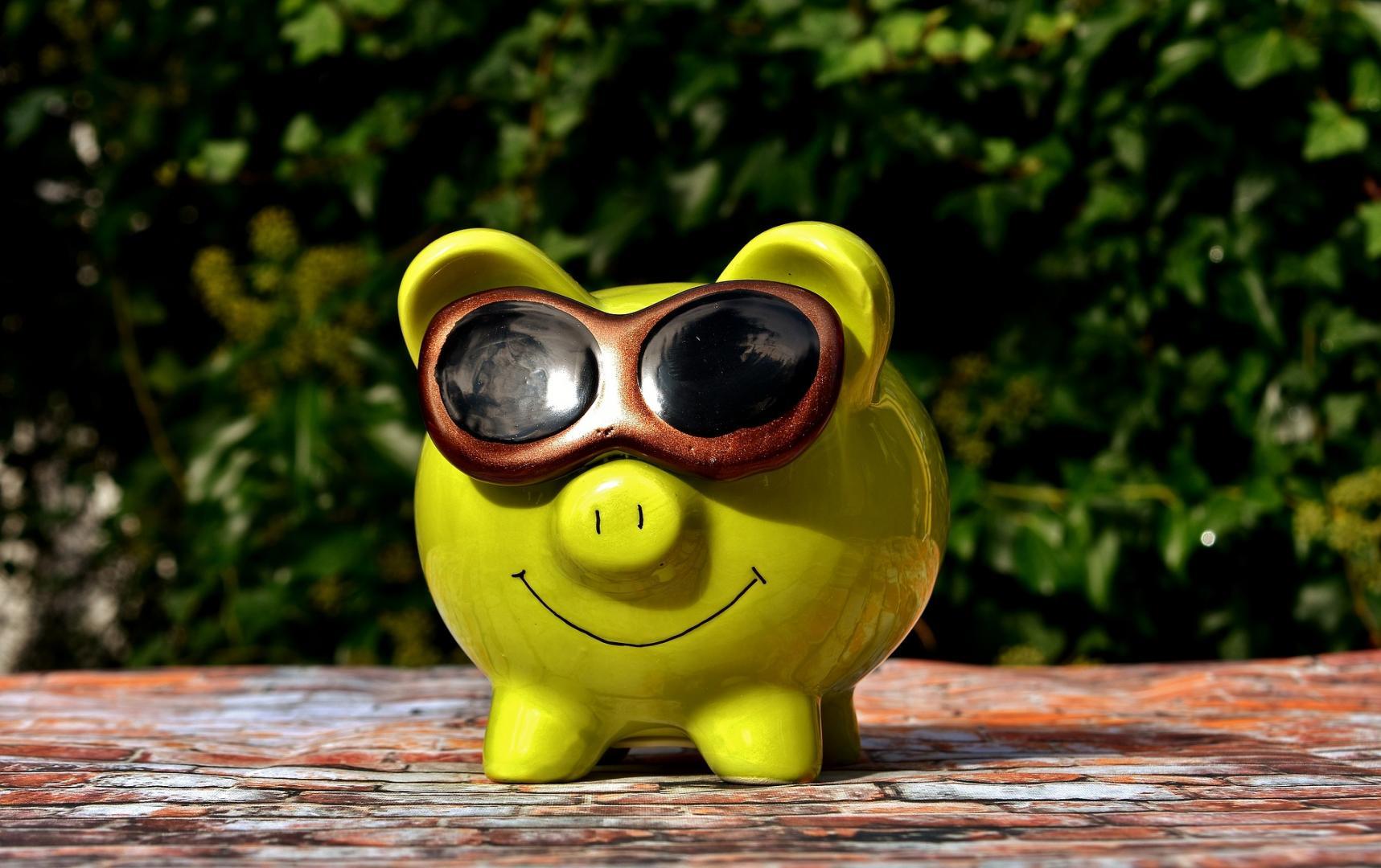 Grünes Sparschwein mit Sonnenbrille