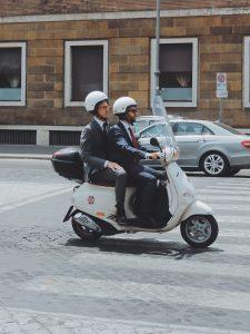 Zwei Männer bilden eine Fahrgemeinschaft, indem sie zusammen auf einem Roller fahren