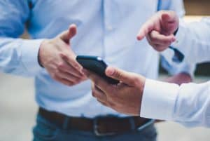 Ein Mann zeigt einem Kollegen das N26 Geschäftskonto auf dem Handy