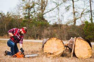 Mann zerschneidet Holz mit einer Säge