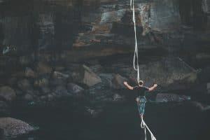 Mann läuft ungesichert auf einen Seil, das über zwei Klippen gespannt ist