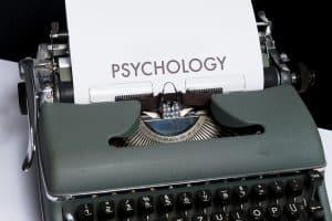 Eine Schreibmaschine schreibt das Wort Psychologie als Sinnbild dafür, dass Psychologie ebenso die Risikotoleranz bei der Geldanlage bestimmt