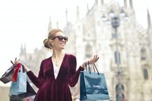 Reiche Frau mit Einkaufstüten in der Hand kommt vom Shopping