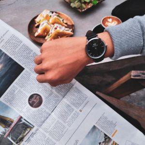 Mann liest Zeitung und schaut dabei auf seine Uhr