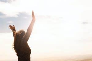 Frau steht frei in der Sonne und hebt die Arme in die Höhe