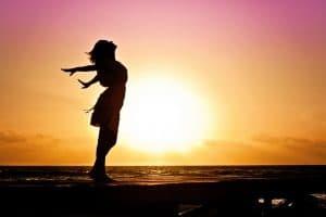 Frau steht im Sonnenuntergang und breitet ihre Arme aus