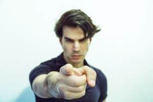 Mann zeigt mit dem Finger in die Kamera