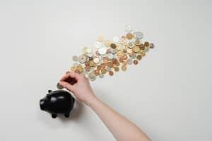 Mann steckt Münzen in ein Sparschwein