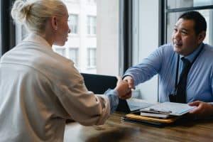 Frau in Gehaltsverhandlung schüttelt ihrem Chef die Hand