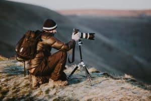 Mann steht auf einer Klippe und fotografiert