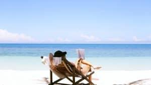 Frau sitzt am Strand und liest ein Buch