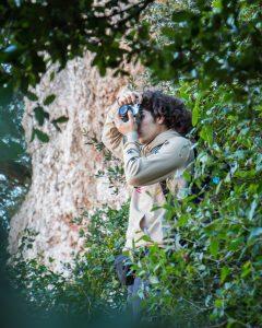 Mann steht mit der Kamera im Gebüsch und verdient mit Fotos Geld