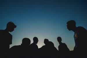 Eine Gruppe von 6 Personen steht im Sonnenuntergang