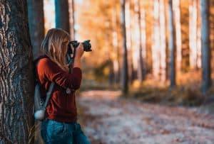 Frau steht im Wald und fotografiert die Bäume