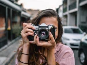 Frau fotografiert mit einer Kamera, um mit Stockfotos Geld zu verdienen