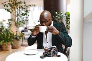 Man sitzt am Tisch, trinkt Kaffee und auf dem Tisch liegt seine Kamera