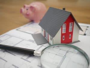 Eine Lupe, ein Sparschwein und hei Haus