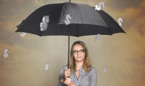 Frau sitzt mit Schirm im Geldregen