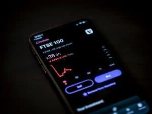 Mann nutzt Trading-App auf seinem Handy