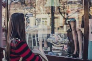 Eine Frau unterliegt ihrer Shoppingsucht und kauft ein