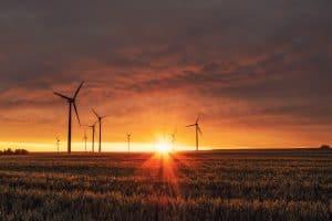 Windräder im Sonnenuntergang, die Miningfarmen und Bitcoin antreiben