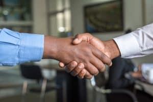 Verkäufer und Käufer schütteln sich nach Verkaufsgespräch die Hand