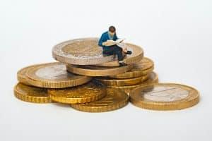 Figur sitzt auf Geldmünzen