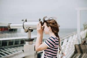 Frau blickt mit einem Fernrohr nach draußen