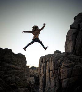 Frau springt über Abgrunf