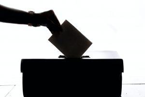 Jemand steht an einer Wahlurne und wählt